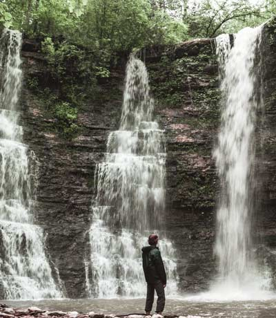 image of man standing in front of waterfalls